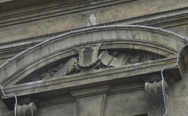 1889 - tympan arrondi, instruments de musique rappelant la vocation de salle des fêtes du premier étage
