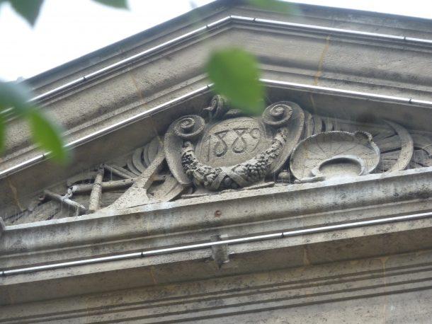 1889 - tympan triangulaire portant la date de construction du bâtiment entourée d'instruments agraires rappelant l'activité principale du village à cette époque
